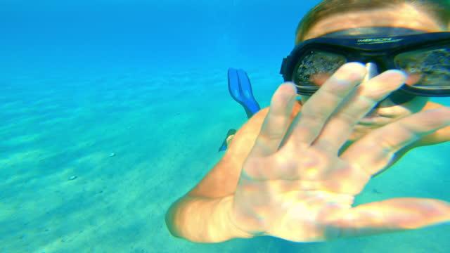 stockvideo's en b-roll-footage met het duiken en het zwemmen van de jongen door in de mooie overzees - zwemvlies
