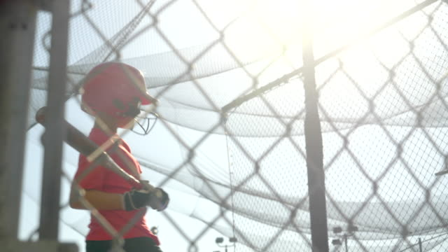 a boy dodges a baseball bad pitch ball and jumps out of the way at the batting cages. - slow motion - gabbia di battuta video stock e b–roll