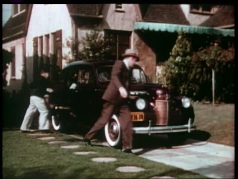 1940 boy + dog get into car in driveway as man walks to driver's door - シボレー点の映像素材/bロール