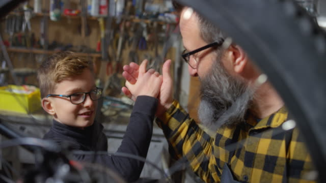 slo mo boy doing a high five with his dad after servicing the bicycle - coat stock videos & royalty-free footage