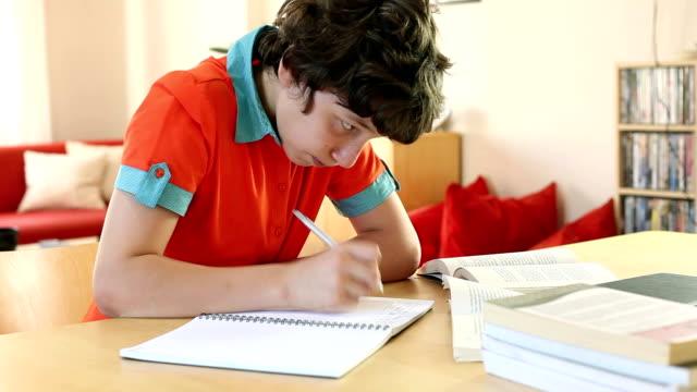 vídeos y material grabado en eventos de stock de niño haciendo los deberes en la mesa de cocina - niño pre escolar