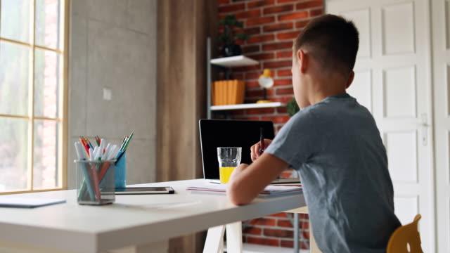 vidéos et rushes de garçon faisant ses devoirs - école