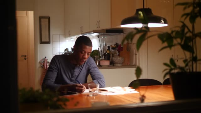 Boy doing homework at illuminated table against kitchen