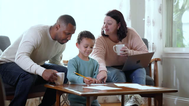 boy doing homework while parents look over his shoulder - arrival stock videos & royalty-free footage