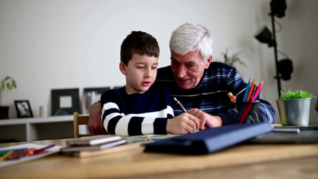 boy doing homework with his grandfather - grandparent stock videos and b-roll footage
