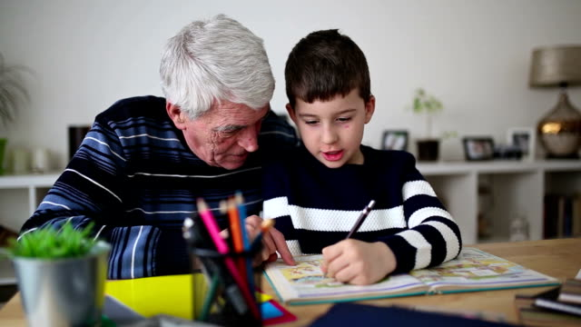 boy doing homework with his grandfather - grandfather stock videos & royalty-free footage