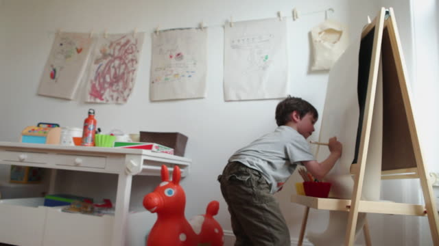 vidéos et rushes de ms boy (4-5) drawing at easel in playroom / brooklyn, new york city, usa - dessin enfant