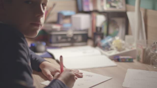 vidéos et rushes de garçon, dessin à la maison, en regardant la caméra - gribouillage