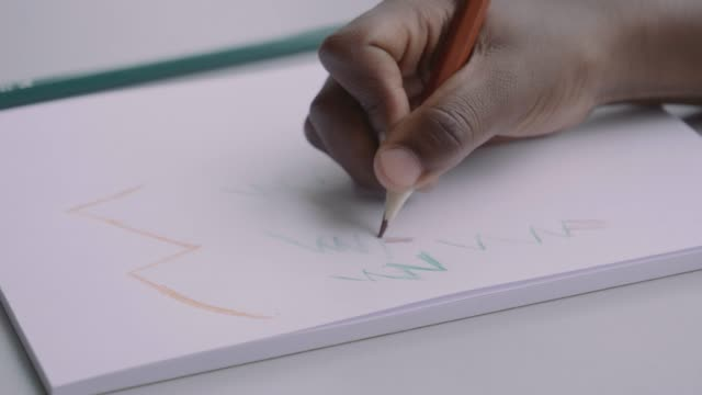 stockvideo's en b-roll-footage met boy drawing with colored pencil in book at school - tekening