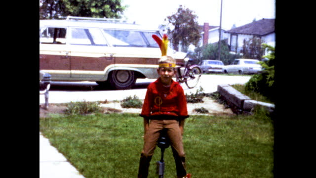 a boy dressed as a native american with a feather headdress walks around his front yard among the bushes and trees - headdress stock videos & royalty-free footage
