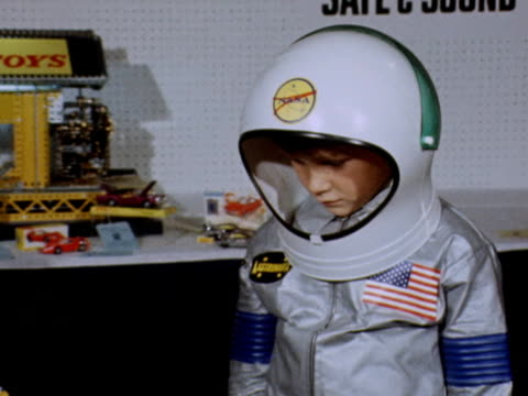 a boy dressed as an astronaut looks at a meccano model of a moon landing craft - 1969 stock videos & royalty-free footage