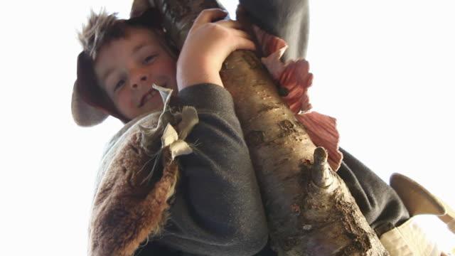stockvideo's en b-roll-footage met boy dressed as bear climbing tree - alleen jongens