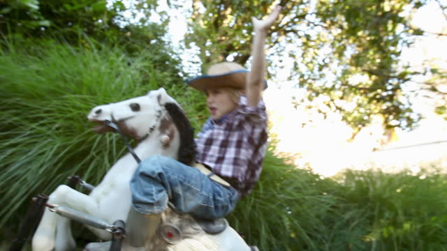 Boy dressed as cowboy on rocking horse