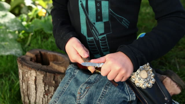 boy dressed as cowboy sharpening stick with penknife - penknife stock videos & royalty-free footage