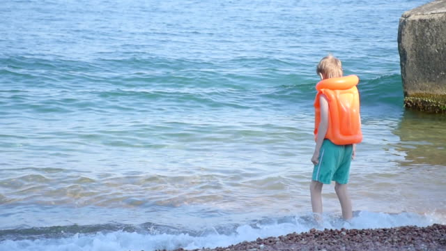 boy dressed in inflatable lifejacket on beach of the sea