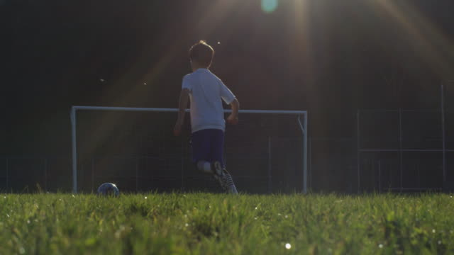 Boy dribbling and shooting soccer ball