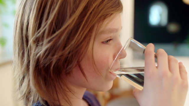 vídeos de stock, filmes e b-roll de boy drinking glas of water in slowmotion - copo