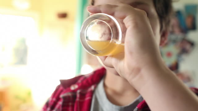 vídeos de stock, filmes e b-roll de boy drinking glass of orange juice - beber
