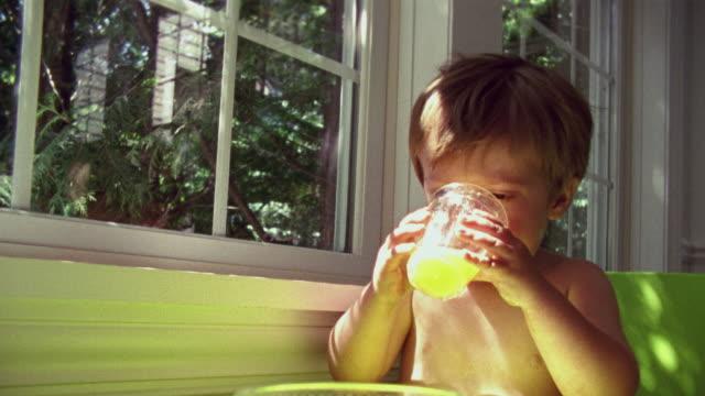 SM CU Boy drinking juice from glass next to window / Minnesota, USA