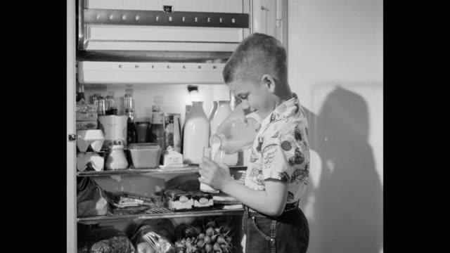 vídeos y material grabado en eventos de stock de boy drinking milk while standing next to open refrigerator in kitchen - encuadre de tres cuartos