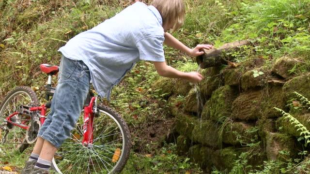 ws boy drinking water with bicycle at forest / tawern, rhineland-palatinate, germany                             - böja sig bildbanksvideor och videomaterial från bakom kulisserna