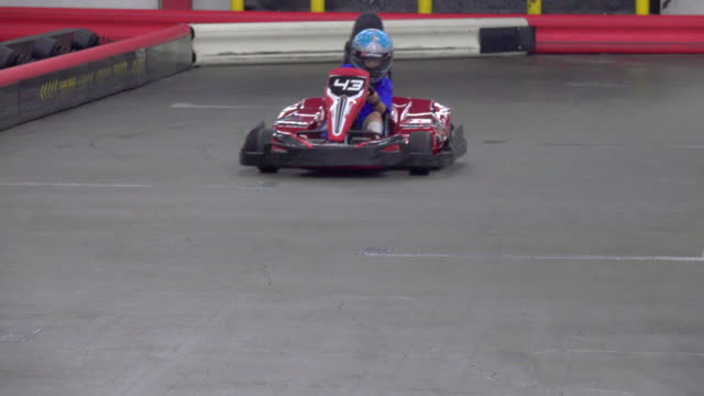 a boy driver races a go kart on a go-kart track. - sports helmet stock videos and b-roll footage