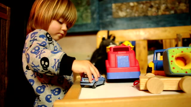 Boy Drives Automobile Toy on Table