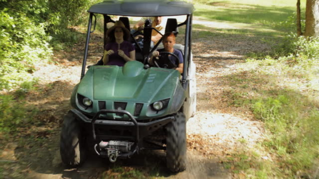 REAR POV Boy (10 -11) driving an ATV and young couple riding as passengers in farm / Madison, Florida, USA