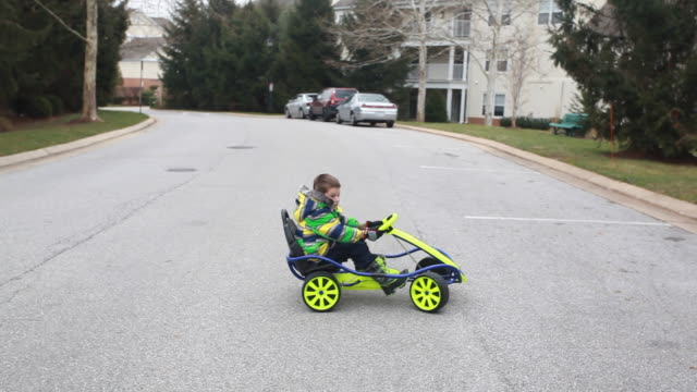 Boy driving go cart in matching winter coat makes a u-turn.