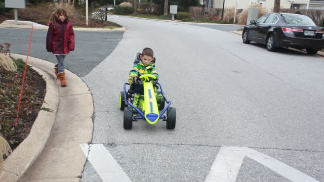 Boy driving gocart drives over speed bump then comes to a stop with sister there.