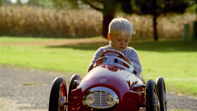 ms, cu, boy (4-5 years) driving toy car on graver driveway, usa, pennsylvania, solebury - spielzeug stock-videos und b-roll-filmmaterial