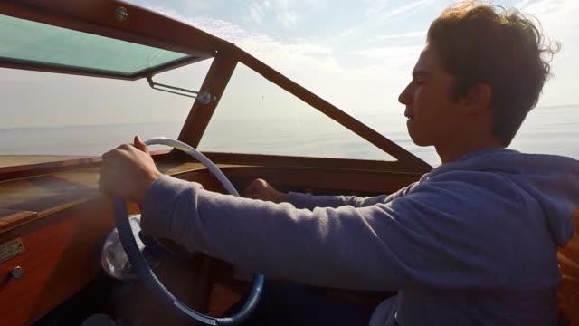 boy driving vintage boat - männlicher teenager allein stock-videos und b-roll-filmmaterial