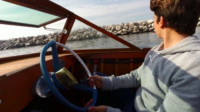 vídeos y material grabado en eventos de stock de boy driving vintage boat - un solo adolescente