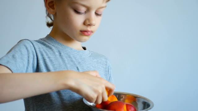 boy eating a peach, close up