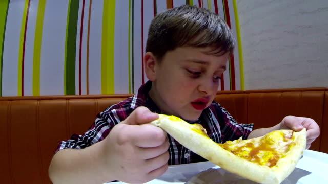 stockvideo's en b-roll-footage met jongen een pizza eten - tafelmanieren