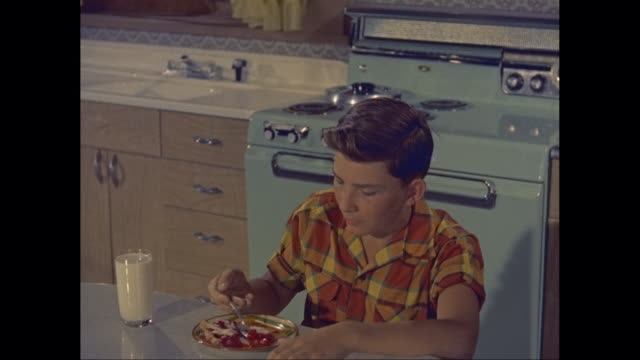 MS Boy eating a slice of cherry pie with a glass of milk at kitchen table / United States