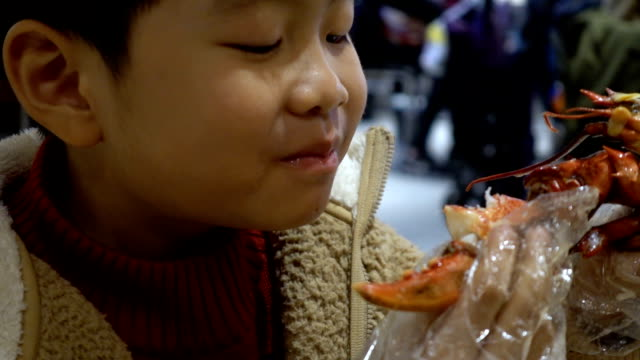 boy eating baked lobster with cheese indoors - lobster seafood stock videos and b-roll footage