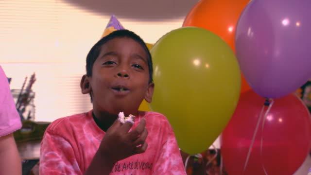 stockvideo's en b-roll-footage met boy eating birthday cake - feestmuts