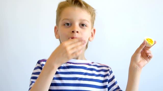 クローズ アップ、ゆで卵を食べる少年