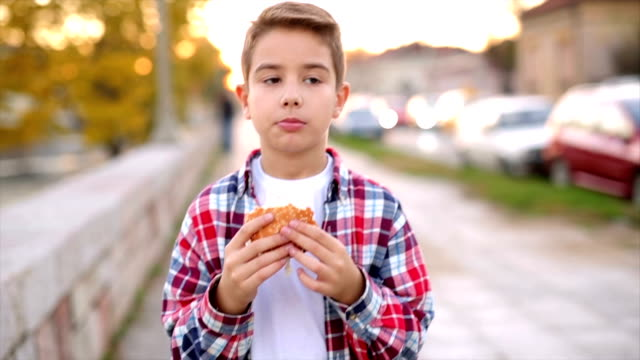 boy eating fast food outdoors - fast food restaurant stock videos & royalty-free footage