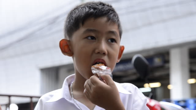 vidéos et rushes de petit garçon manger poulet frit - se mordre les lèvres
