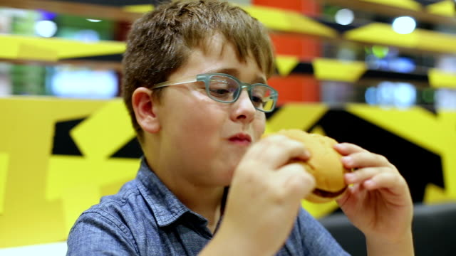 boy eating hamburger - overweight child stock videos & royalty-free footage