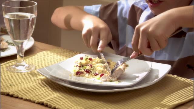 vídeos y material grabado en eventos de stock de boy eating healthy lunch with family at kitchen table - modales de mesa