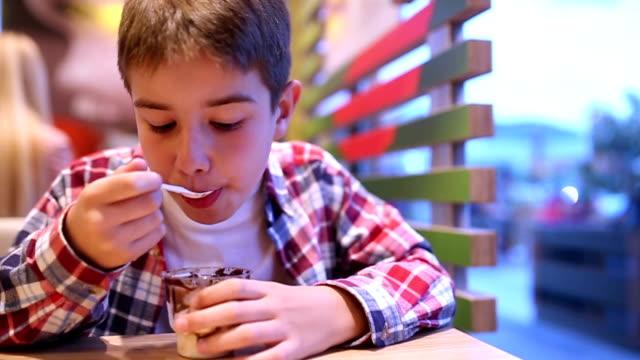 Pojke som äter glass i caféet