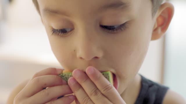 stockvideo's en b-roll-footage met boy eating melon - alleen jongens