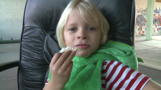 cu boy (6-7) eating rice cracker sitting on armchair, gent, belgium - cracker stock videos and b-roll footage