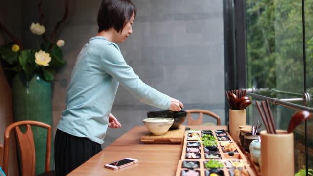 vidéos et rushes de le garçon mange des nouilles de riz avec des baguettes - bol à soupe