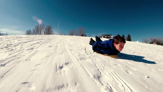 vídeos y material grabado en eventos de stock de chico disfruta de nieve trineo - tobogan