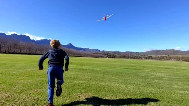 boy enjoys throwing his toy plane on the field - model aeroplane stock videos & royalty-free footage