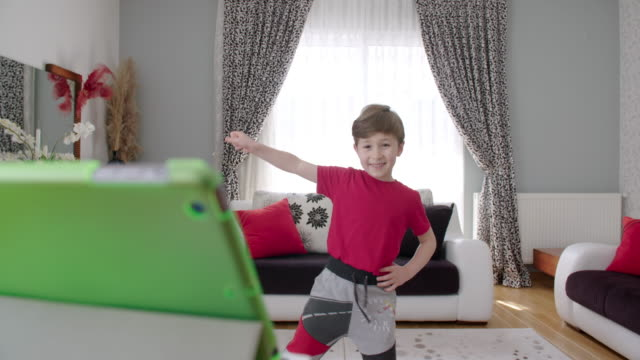 boy exercising in conjunction with a digital tablet - one boy only stock videos & royalty-free footage